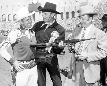Randolph Scott and an official of the annual Sheriff's Rodeo at the L. A. Colisseum make a rifle and ribbon presentation to Gene Autry. (Thanx to Bobby Copeland.)