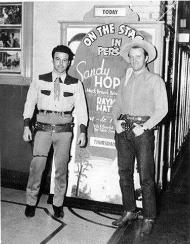 "Anybody recognize these two gentlemen posed before the in-person placard for Raymond Hatton? Not sure where the theater was but the photographer was Charles Pugh of Erwin, Tennessee, in 1946. (Note the lobby cards for ""Desert Horseman"" with Charles Starrett on the left. (Thanx to John Bickler.)"