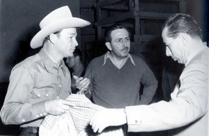 "Roy Rogers meets with Walt Disney (center) and a Disney costumer preparing for Roy's role in the ""Pecos Bill"" segment of ""Melody Time"" ('48)."