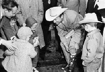 Roy Rogers shows his boots to a group of young fans in Nashville, Tennessee.