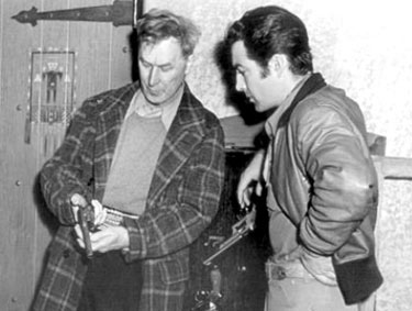 "William S. Hart gives a little firearm instruction to Robert Taylor during the making of ""Billy the Kid"" ('41 MGM)."