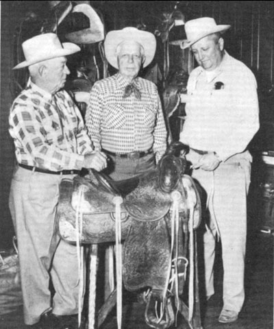 Hoot Gibson, in 1958, with the Hamley Trophy saddle he won as All Around Champion Cowboy at the 1912 Pendleton Round-Up. That was the first time such an award had been up for grabs. Hoot had entered five events, saddle bronc riding and the relay, pony express, roman, and wild horse races. Shown with Hoot are Lester Hamley (left), owner of Hamley and Company and Jack Stangier (right), president of the Pendleton Round-Up.