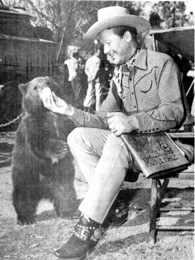 "During a break in the filming of ""Home on the Range"", Monte Hale takes an opportunity to feed the bear. Note the leather script cover under Monte's arm."