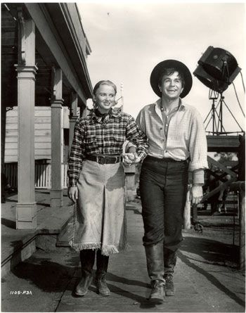 "Jeanne Kelly and Noah Beery Jr. take a stroll on the Universal back lot between scenes of ""Riders of Death Valley"" ('41)."