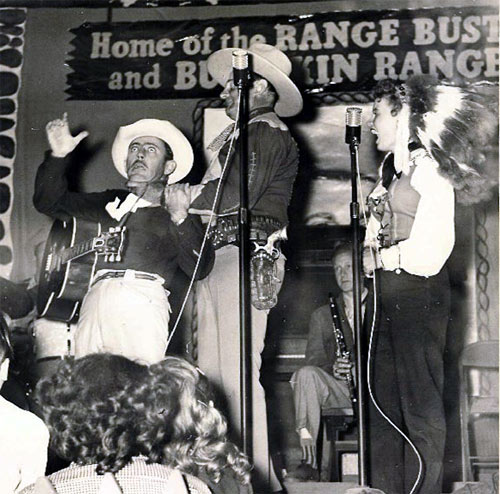 "The Broome Brothers (Joe, Lee and Ray) used to be Ray ""Crash"" Corrigan's band at Corriganville in the '50s. Here Lee Broome does a routine with Crash and his wife Elaine Dupont. Note the sign refers to both Corrigan's Range Busters and his unsold TV pilot ""Buckskin Rangers"". (Photo courtesy Ron Broome.)"