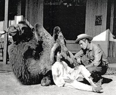 "Child actor Ricky Vera snuggles up to a camel and talks with ""Broken Arrow"" series star John Lupton between scenes of the December 1956 episode ""Cry Wolf""."