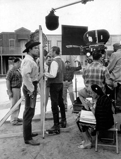 "Clint ""Cheyenne"" Walker on the Warner Bros. back lot. That's Clyde Howdy, Clint's stand-in and a sometime actor, looking the other way. Note the little old lady script supervisor seated in front of Clint."