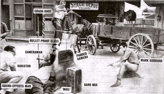 "How it's done. Mark Goddard, Culley on ""Johnny Ringo"", blazes away while the cameraman, the director and a sound effects man cower behind sand bags and bullet proof glass. Extra bullet holes are provided by crack shot Jim Rug."
