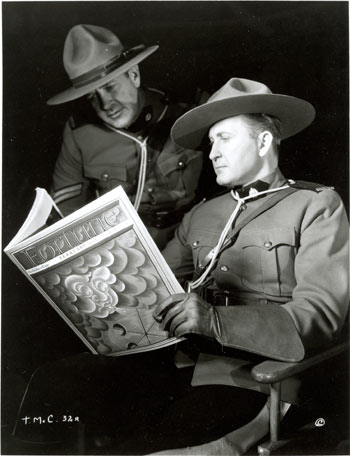 "Tim McCoy and another actor take a break from filming ""Fighting Shadows"" ('35 Columbia) to glance at the February '35 copy of FORTUNE magazine."