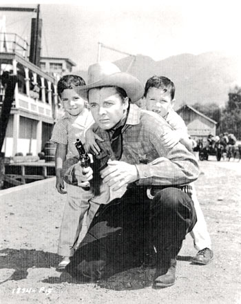 "Terry, 6, and James Shannon, 4, seek protection behind their father Audie Murphy in this posed photo on the set of ""Ride a Crooked Trail"" ('58 Universal)."
