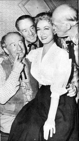 "In between scenes for TV's ""Cimarron City"", Audrey Totter is surrounded by former silent comedians, Hank Mann, Snub Pollard and Matthew McCue, all of whom now work as extras on the series."