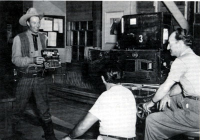 "Bill Elliott holds a slate for the next scene of ""The Fabulous Texan"" ('47) for Republic cinematographer Jack Marta."