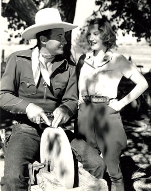 "Ray ""Crash"" Corrigan instructs leading lady June Martell how to sharpen a knife during a break from ""Wild Horse Rodeo"" ('37 Republic)."