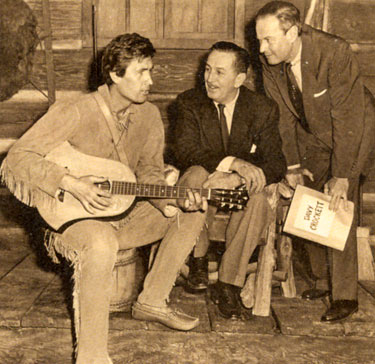 "Fess Parker tunes up his guitar for producer Walt Disney and director Norman Foster of 1955's ""Davy Crockett, King of the Wild Frontier""."