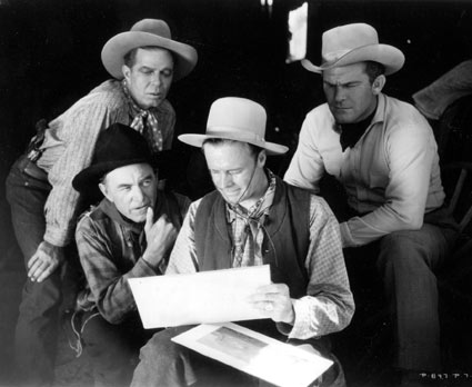 "Hoot Gibson, Harry Carey and Guinn ""Big Boy"" Williams watch Wally Wales put finishing touches on a western landscape painting during a break in the filming of ""Powdersmoke Range"" ('35)."