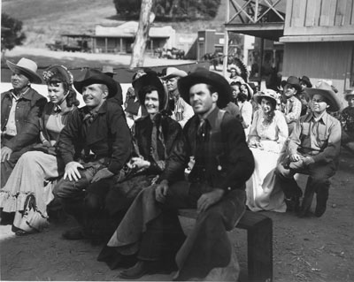 "Photo taken during the making of ""Lawless Rider"" ('54 U.A.) with Johnny Carpenter (third from left). Stuntman/actor Lou Roberson is on the right. Roberson was stuntman Chuck Roberson's brother. Known in the business as a 'high man', he was killed in a bar fight in the '70s. Producer Alex Gordon, who also was an extra in the film, is behind Roberson in the large hat. (Thanx to Tom Weaver.)"