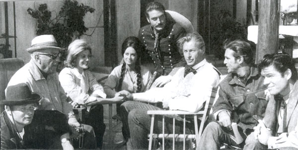 "Relaxing between takes of ""Pyramids of the Sun God"", filmed in Yugoslavia in '65, are (L-R) Ralf Wolter, director Robert Siodmak, Tita Barker, Theresa Lorca, Rik Battaglia, Lex Barker , Gustavo Rojo and Kelo Henderson (former star of TV's ""26 Men"")."