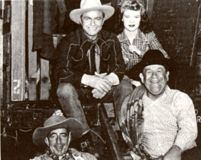 "Taking a break from filming Republic's ""Outlaws of Santa Fe"" ('44) are Don Barry, Helen Talbot, Wally Vernon and noted Indian athlete Jim Thorpe."