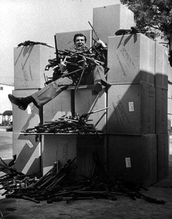 "Hugh O'Brian in July '57 sitting on boxloads of toy Buntline Special guns promoted on his ""Life and Legend of Wyatt Earp"" TV series."