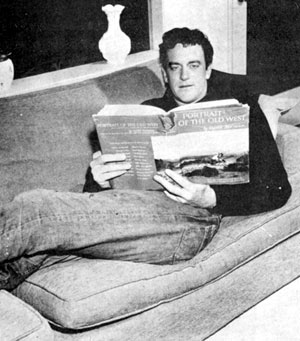 "Relaxing at home, James Arness, star of TV's long running ""Gunsmoke"", brushes up on his western history by reading a copy of PORTRAIT OF THE OLD WEST by Harold McCracken, first published in 1952."
