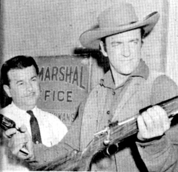 James Arness compares his sixshooter with a new Mauser rifle while on a practice shoot at the Los Angeles Police Academy Pistol Range in 1959.