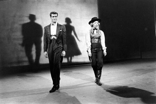 "Hugh O'Brian and Dinah Shore doing a shadow dance on the ""Dinah Shore Show"". Note the Wyatt Earp shadow behind Hugh and Dinah with a dress."