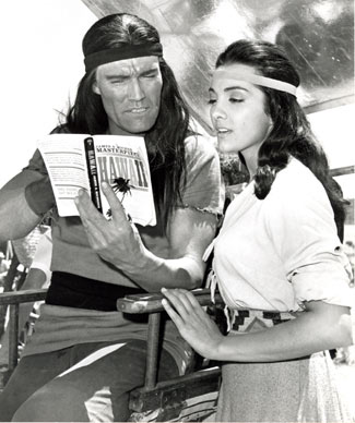 "Chuck Connors and Kamala Devi take a break from filming ""Geronimo"" ('62 U.A.) to read a bit of James A. Michner's HAWAII. Connors and Devi fell in love while making the movie and were married from April 10, 1963 to 1972. (Thanx to Neil Summers.)"
