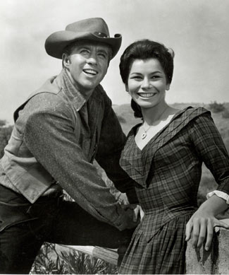 "Clu Gulager as Deputy Ryker and Diane Roter as Jennifer take a break from filming ""The Virginian"" during the '65-'66 season."