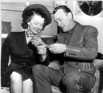In 1947 Roy measures the finger of his bride-to-be, Dale Evans, for a ring.