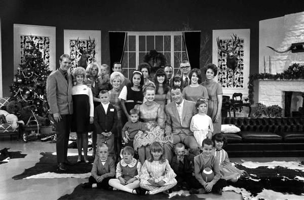 "Roy and Dale with six children, four spouses at the time and 13 grandchildren at a taping of the ""Jonathan Winters Christmas Show"" in December 1968. (L-R) Dusty, Linda Yoder Rogers (no children as they married 11/67), Linda Rogers Johnson holding her son Robin Roy with husband Gary Johnson, Mimi Easton Swift in front of Johnson (she was then widowed and had not married Swift yet), Dodie is next to Mimi with white headband, Cheryl Rogers Rose Barnett, her first husband Bill Rose. Next to Bill is Tom and Barbara Fox on far right. Tom and Barbara's three girls are in front of them--Candy with the long hair, Julie and Mindy with short hair. Nine grandchildren are in front."