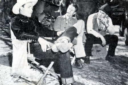 "At Republic, Roy takes a break with director Frank McDonald (with pipe in mouth) while filming ""Rainbow Over Texas"" ('46)."