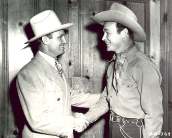 "There's certainly no ""feud"" here as Republic's two top cowboys shake hands. Gene Autry and Roy Rogers."