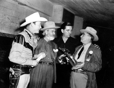 "L.A. Sheriff Gene Biscailuz shows Roy, Gabby Hayes and Stuart Hamblin the award to be used at the ""Western Hall of Fame Hoss Opera"" held at L.A.'s Olympic Auditorium 11/28/48."