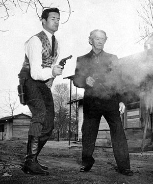 "Hugh O'Brian, TV's ""Wyatt Earp"", and real life badman Al Jennings, 93, draw and fire for a LOS ANGELES TIMES photo in 1957."