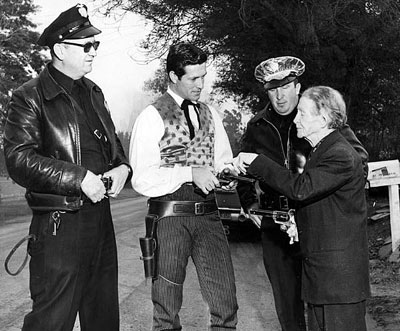 When neighbors became alarmed over the above gunfire, police were called. Here officers Melbie and Henkin observe as Al Jennings shows Hugh O'Brian how Colts were handled in the old days.