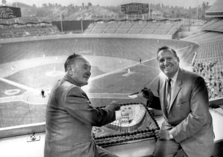Angels General Manager Fred Haney and Chairman of the Board Gene Autry celebrate the last game the team played in Dodger Stadium as a home team by cutting a cake in the press box during a double header. The cake is decorated with a replica of the Angels' new stadium in Anaheim.