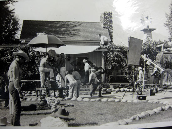 "Hopalong Cassidy (William Boyd) stands in the doorway of the Wofford Ranch house at Kernville, CA, as the crew prepares for a shot. This may be from Hoppys ""The Showdown"" as it was partially filmed on the Wofford Ranch. (Thanx to Bobby Copeland for the photo and Tinsley Yarbrough for the location ID.)"