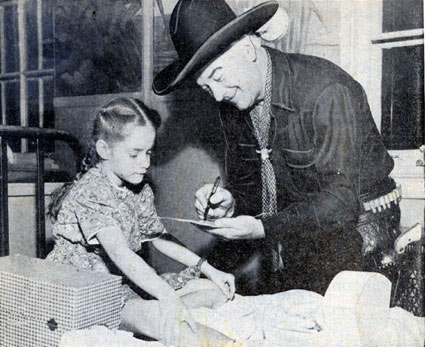 Hopalong Cassidy signs an autograph for Georgia, a young patient at the Shriner's Hospital for Crippled Children in Chicago in 1950.