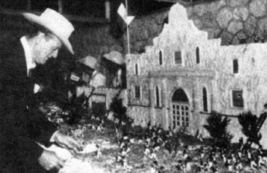 "In November 1960 John Wayne slices the first piece of a 30 ft. ""The Alamo"" premiere cake which recreated the attack of the Alamo."