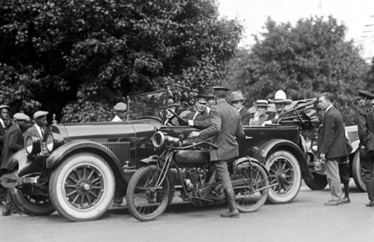Cars of the Stars: A crowd gathers as Tom Mix is stopped for speeding in 1925. (Thanx to Bobby Copeland.)