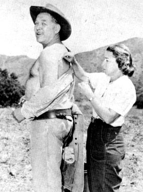 "Nurse Maxine Schulze administers first aid to Ward Bond for a cut he received while on location for ""Wagon Train"" in 1960."