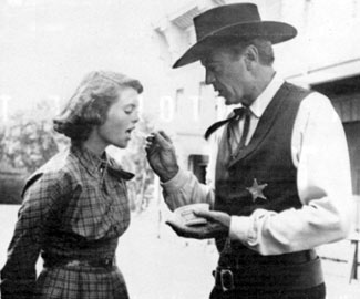 "Gary Cooper gives daughter Maria Cooper Janis a bite of his snack on the set of ""High Noon"" ('52)."