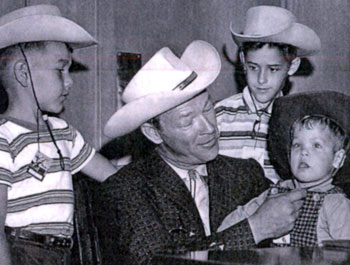 Roy Rogers helps a young fan cinch up his hat string. (Thanx to Colin Jellicoe.)