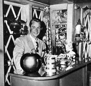 Alan Ladd stands behind his home bar decorated with posters from his films. Photo taken in late 1944.