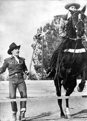 At his Heaven on Earth Ranch, Johnny Carpenter helps blind Jimmie Pruett over the jump on horseback. This builds great moral for handicapped kids.