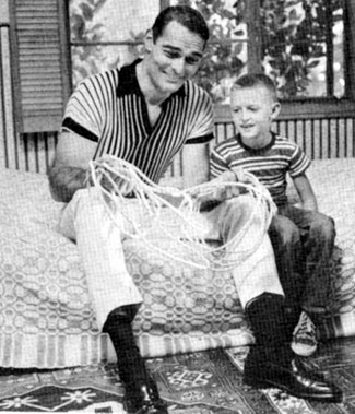 "At home, John (""Lawman"") Russell shows son John James, age 7, some rope tricks."