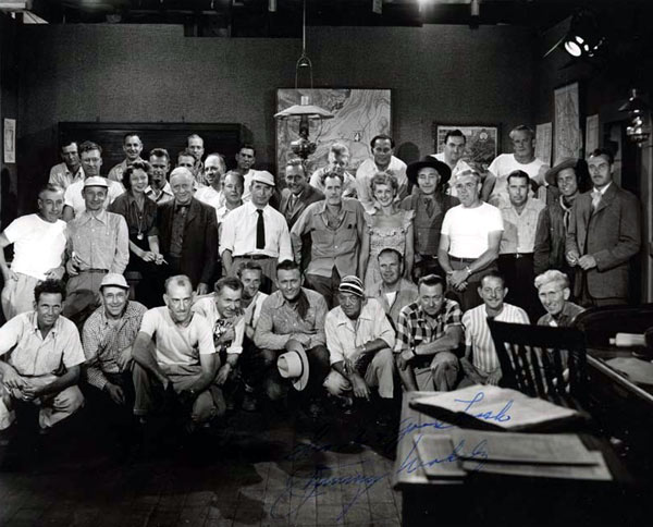 "For Jimmy Wakely's last Monogram western in 1949, ""Lawless Code"", this partial cast and crew photo was taken. You can easily spot Jimmy, director Oliver Drake (with mustache and open shirt collar behind Jimmy), Myron Healey to the right of Ollie, leading lady Ellen Hall to the left of Ollie, Kenne Duncan to Ellen's left, Steve Clark to Ollie's right in dark coat, Terry Frost and Tris Coffin standing to the right. Set continuity lady Helen McCaffrey is to the right of Steve Clark. We're also sure Assistant Director Eddie Davis and Cinematographer Harry Neumann are in the group but unsure which two they may be. A good guess would be the man kneeling to the left of Jimmy and the man standing to the right of Drake. Note Wakely's autograph on the photo. (Photo courtesy Bobby Copeland.)"