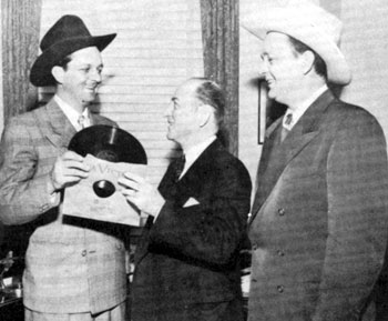 "Bill (Cowboy Rambler) Boyd watches as his brother Jim presents an official recording of ""Palace in Dallas"" to Mayor Rogers of Dallas, TX, sometime in the late '40s."
