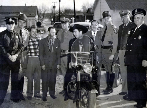 "Fuzzy St. John seems to be saying, ""How come you get to ride on the motorcycle?"" Unsure of the city in which this law enforcement group photo was taken. (Thanx to Jerry Whittington.)"