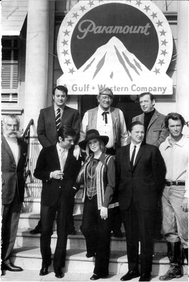"Paramount executives pose with stars that were making productions on the studio lot in 1969. (Front row, l-r) Lee Marvin (""Paint Your Wagon""), Paramount VP Robert Evans, Barbra Streisand (""On a Clear Day You Can See Forever""), Paramount VP Bernard Donnenfeld, Clint Eastwood (""Paint Your Wagon""). (Top row, l-r) Rock Hudson (""Darling Lili""), John Wayne (""True Grit""), Yves Montand (""On a Clear Day You Can See Forever""). (Thanx to Frank Story.)"